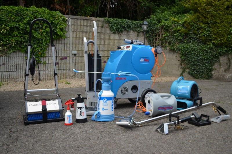 cleaning chemicals and equipment laid out in a driveway