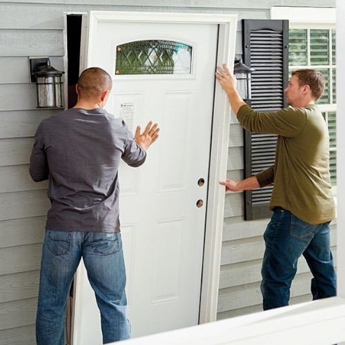 two men fitting a newly painted door to a house