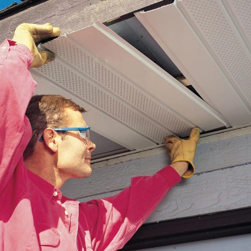 a man installing new soffits and fascias on a house