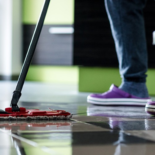 a tiled floor being mopped by a person in purple shoes