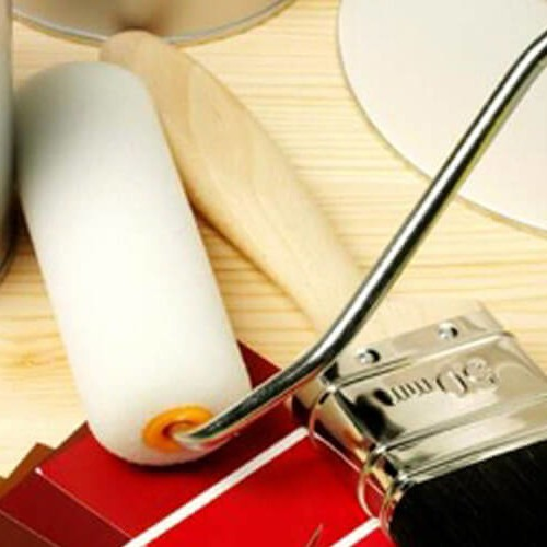 Interior painting and decorating equipment and brushes on a wooden background