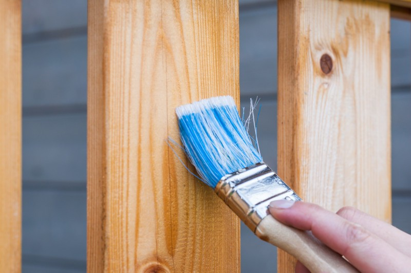 a wooden fence being painted with blue paint