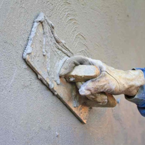 a person applying plaster to a wall