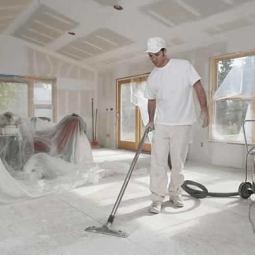 a man in white clothing cleaning an apartment after building work has been carried out