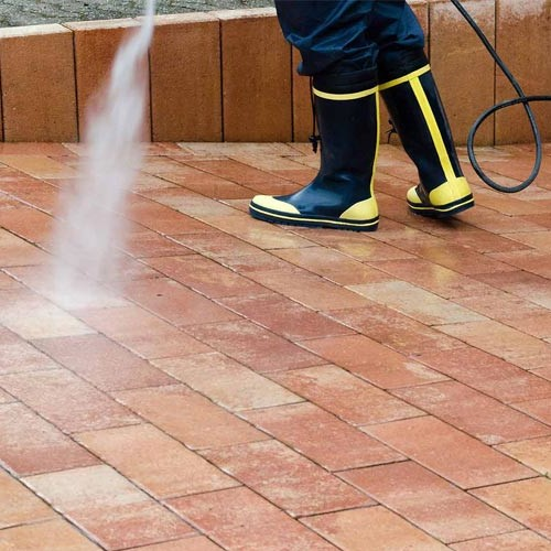 a person spraying cleaning solution onto a stone floor