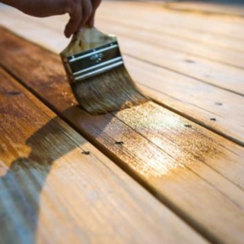 a person painting varnish on to a wooden deck